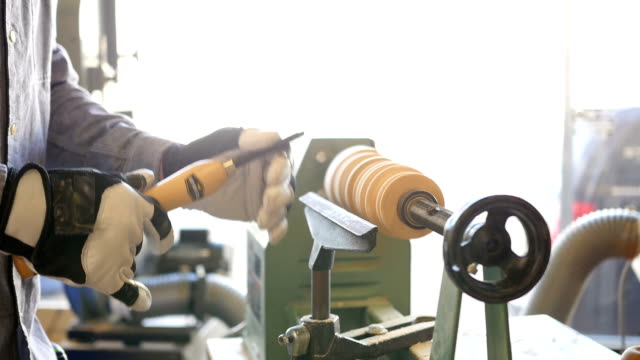 Man uses lathe in community woodworking workshop video