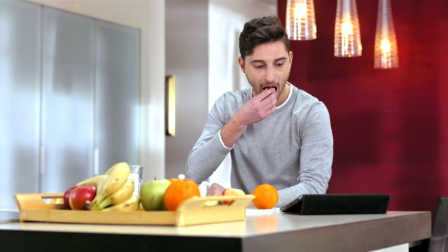 Man Using A Digital Tablet During Breakfast video
