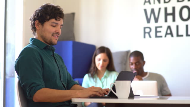 Man using a laptop in a modern office video
