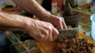 A man using a meat cleaver chopping cooked chicken livers in slow motion video