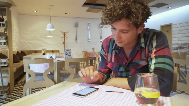 Man using a smart phone in a bistro cafe. video