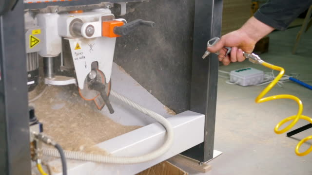 man using air compressor system to blow sawdust, slow motion video