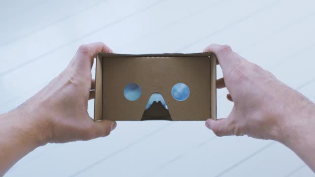 Man using Cardboard Virtual Reality Glasses POV video