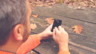 Man using cellphone on a bench in the park. video