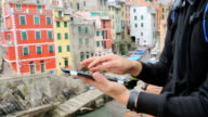 Man using digital tablet at Riomaggiore fisherman village background. video