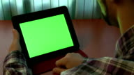 Man using digital tablet with a green screen video