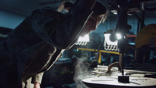 Man Using Drill Press in Shadowy Workshop video