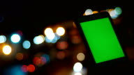 Man using Green Screen Tablet in Night with Defocus of Traffic Lights video