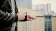 Man using his smartwatch touchscreen standing on the roof, then walks away. hands closeup. FullHD video