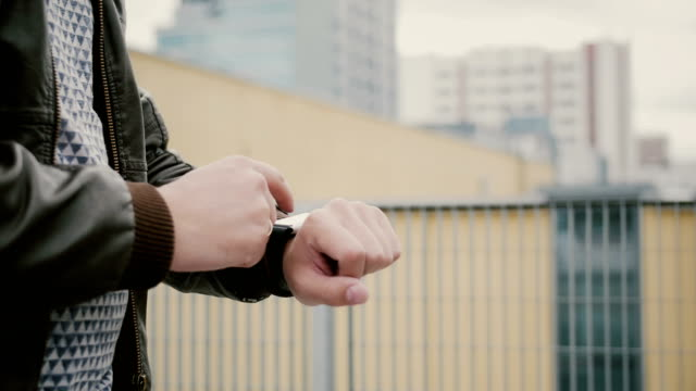 Man using his smartwatch touchscreen standing on the roof, then walks away. hands closeup. 4k video