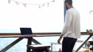 man using laptop computer at outdoor cafe video