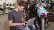 Man using laptop near motorcycle video