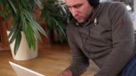 Man Using Laptop Wearing Headphones video