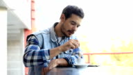 Man using mobile smart phone and drink coffee in cafe video