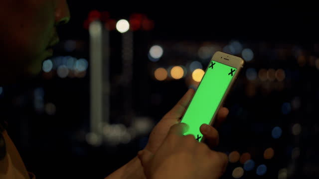 A man using smartphone at night on the top of the building with bokeh background video
