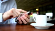 Man Using Smartphone in a Cafe. video