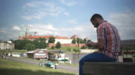 Man using smartphone sitting on wall by the river video