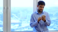 Man using smartphone standing by window at evening video
