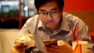 man using smartphone while eating hamburger video