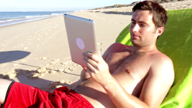 Man Using Tablet Computer On Sun Lounger video
