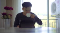 Man Using Tablet PC and Drinking Coffee video