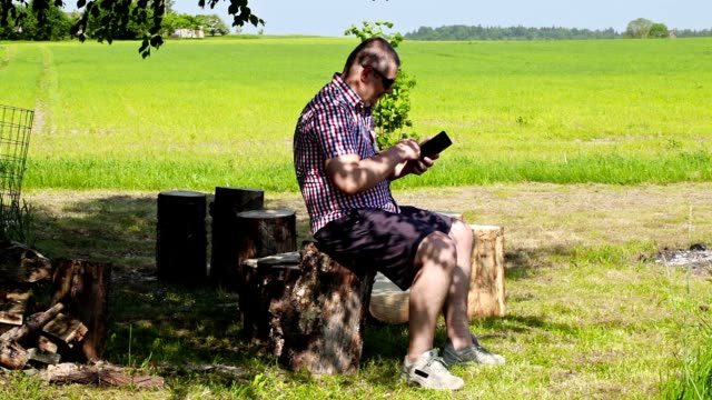 Man using tablet PC under the tree in summer video