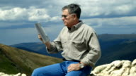 man using tablet pc while on a mountain video