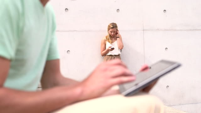 Man using tablet while woman listening music in background video
