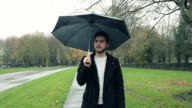 man waiting in the rain with an umbrella video