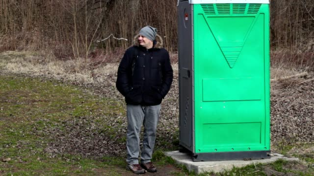 Man waiting near green portable toilet in the park video