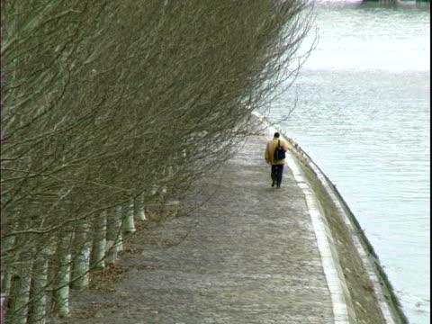 Man walking alone along Seine in Paris video