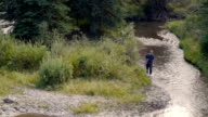 A man walking along a stream or river with a fishing pole in his hand video
