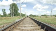 Man walking along railway tracks toward camera video