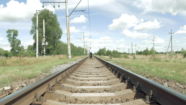 Man walking along railway tracks toward camera video
