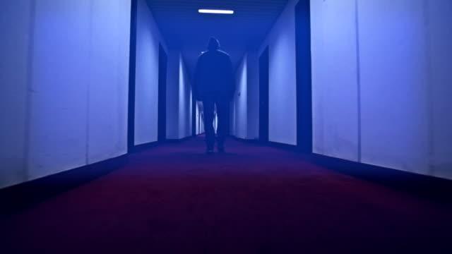 Man walking in a creepy hotel corridor video