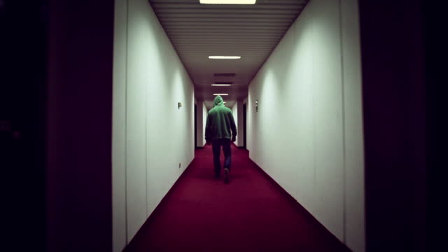Man walking in a creepy hotel corridor video