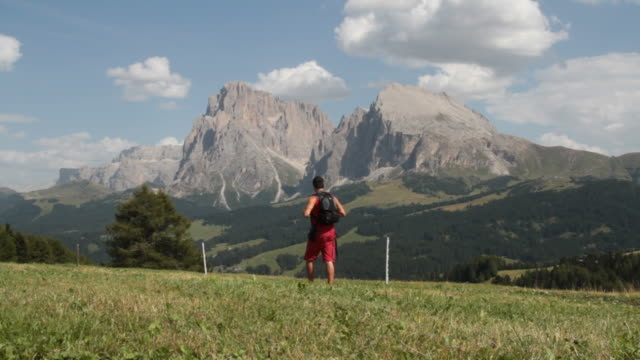 Man walking in Dolomites Sasso Lungo and Piatto on background video