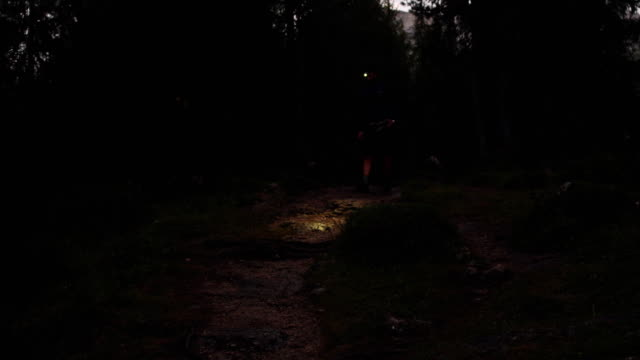 man walking in forest by night with headlamp light. Group of friends summer adventure journey in mountain nature outdoors. Travel exploring Alps, Dolomites, Italy. 4k slow motion 60p video video