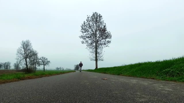 Man walking on country road in winter season video