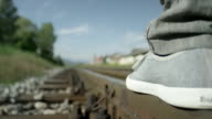 SLOW MOTION CLOSE UP: Man walking on railroad track video
