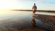 Man walking on the edge of the Gulf of Finland video