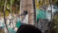 Man walking over a hanging bridge across a mountain stream video