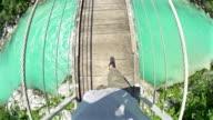 Man walking over a hanging bridge video