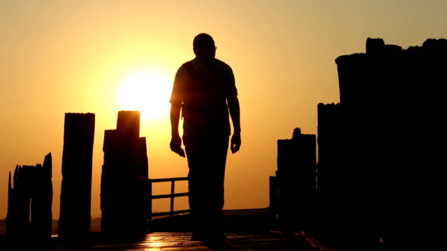 Man Walking Over Wooden Bridge in Sunset video