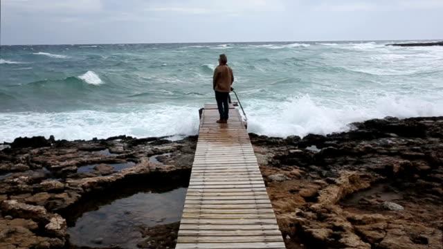 Man walks along boardwalk above sea, looks off video