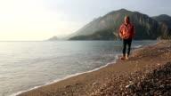 Man walks along deserted beach below mountains, sunrise video