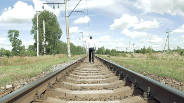 Man walks along railway tracks in the countryside video