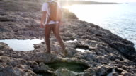 Man walks along rocky coastline towards sunrise video