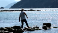 Man walks along rocky pier into sea shallows, looks off video