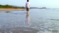 Man walks along the ocean summer heat video